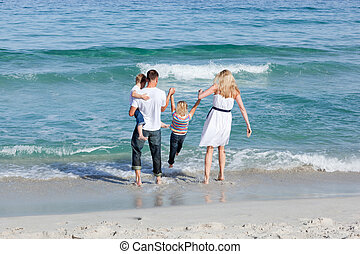 Jolly family walking on the sand