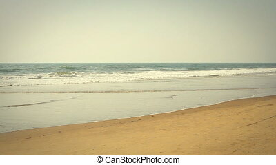 waves touching sandy beach at sunny day
