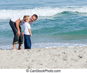 Affectionate father talking with his son at the beach