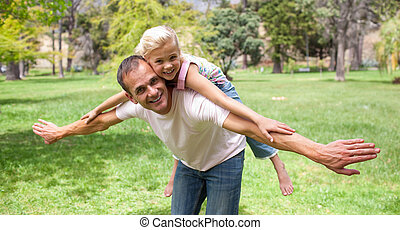Adorable little girl having fun with her father in a park