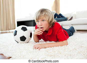 Animated boy watching football match lying on the floor