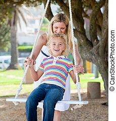 Cheerful mother pushing her child on a swing