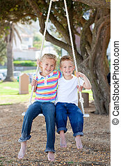 Cheerful siblings swinging in a park