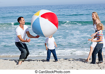 Lively family playing with a ball at the beach