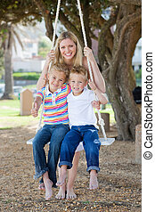Smiling mother and her children swinging