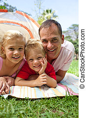 Happy father and his children lying on the grass in a park