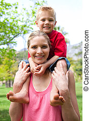 Cheerful mother giving her son piggy-back ride in a park
