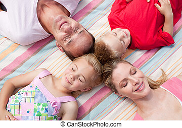 Loving family sleeping lying on the grass in a park