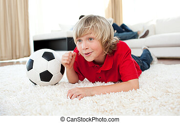 Excited boy watching football match lying on the floor in...