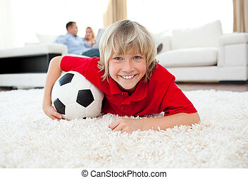 Smiling boy watching football match lying on the floor in...