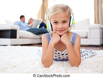 Smiling little girl listening music lying on the floor in...