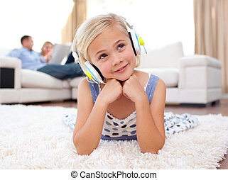 Merry little girl listening music lying on the floor in the...