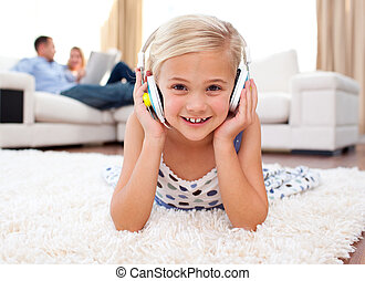 Happy little girl listening music lying on the floor in the...