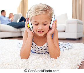 Cute little girl listening music lying on the floor in the...