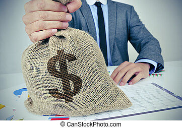 young man in suit with a burlap money bag with the US dollar sign
