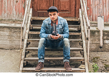 Man sitting on a wooden staircase. Old house