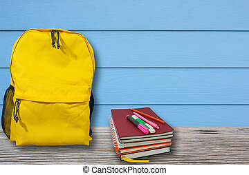 Backpack and notebook is placed on a wooden table with blue wall.