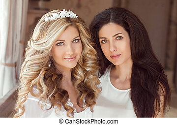 Healthy hair. Two beautiful girls. Brunette stylist and smiling blond girl bride with long curly hairstyle and bridal makeup. Wedding indoor portrait.