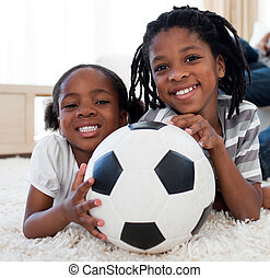Cheerful siblings holding a ball lying on the floor in the...