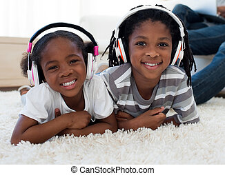 Adorable siblings listening music in the living room