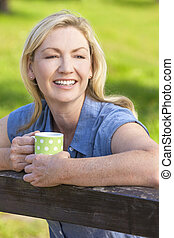 Woman Resting on Fence Drinking Tea or Coffee