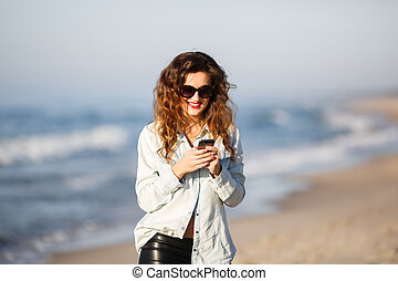 Woman sending an SMS while relaxing on the beach at autumn...