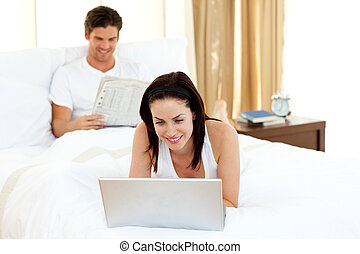 Woman using laptop on her bed - Woman using laptop lying on...