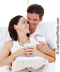 Radiant couple drinking coffee lying in the bed at home