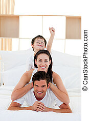 Cute boy and his parents having fun lying on the bed