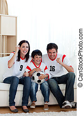 Cheerful family watching football match on television
