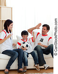 Joyful family watching football match on television