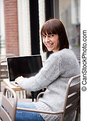 Middle aged woman sitting outside using laptop