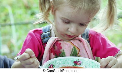 Girl eating with spoon - Girl on nature of spoon eating soup