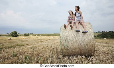 Two girl sits on haystack. - Young happy children sitting on...