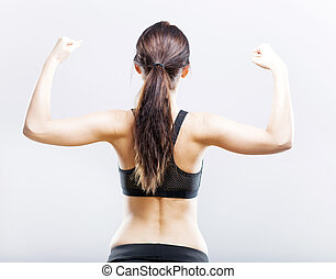 Fit woman flexing her biceps, back view - Young fit woman...