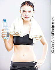 Woman after fitness class with water bottle and towel