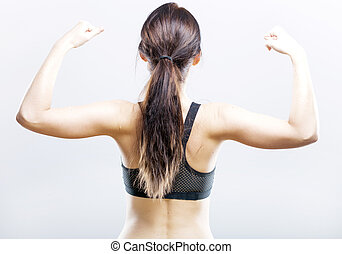 Fit woman flexing her biceps, rear view - Young fit woman...
