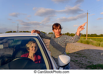 Woman giving directions to a female driver who has lost her...
