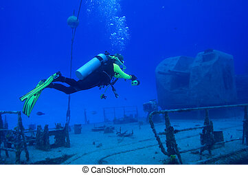 Diver explores warship - A diver is hovering in front of a...