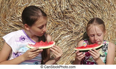 Two girls eating watermelon near the haystack - Young happy...