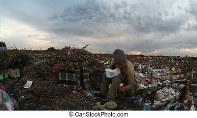 man unemployed homeless dirty looking food waste in dump...