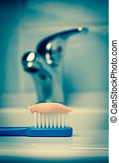 Blue toothbrush with paste in bathroom on sink