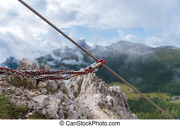 Close up view of two carabiners with dolomites on the background