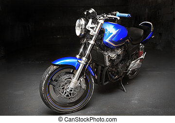 blue motorcycle - powerful blue motorcycle against a dark...