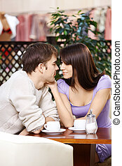 Enamoured - Loving couple talks behind a little table in...