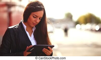 brunette girl playing on a tablet in the street a woman behind a red background