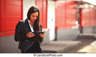 brunette girl playing on tablet in the street woman behind a red background
