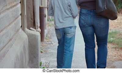 Mother and son together outdoors walking in the street rear view