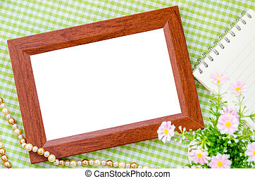 Wooden photo frame with flower on beautiful background.