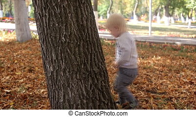 boy jumping beside a tree